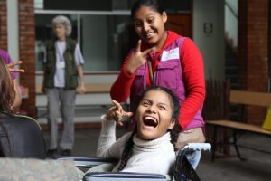 A young person in a wheelchair with a big smile